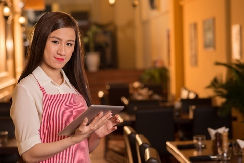 waiter taking a customer's order at the table on an ipad tablet