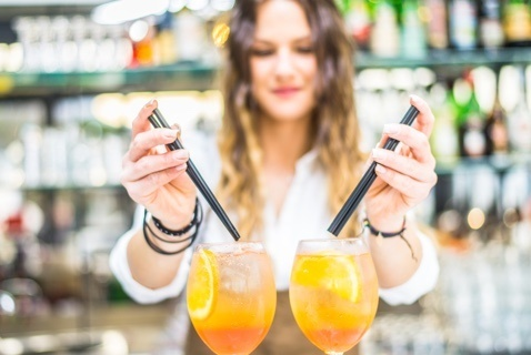 Image of a busy bartender mixing a couple drinks for customers