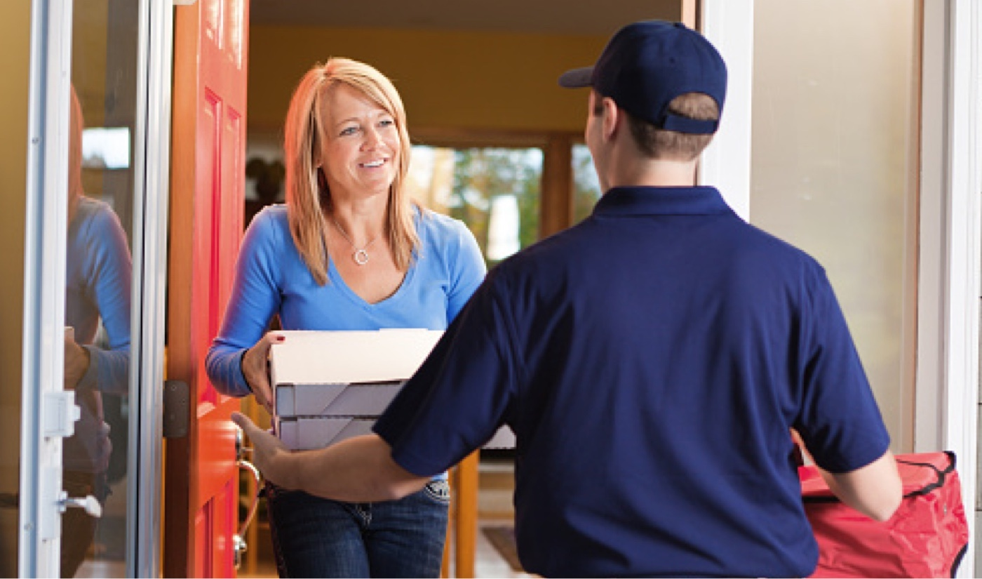 delivery guy handing pizzas to a customer